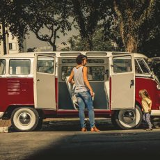 background image with a red vw kombi model t1 and family at sao paulo